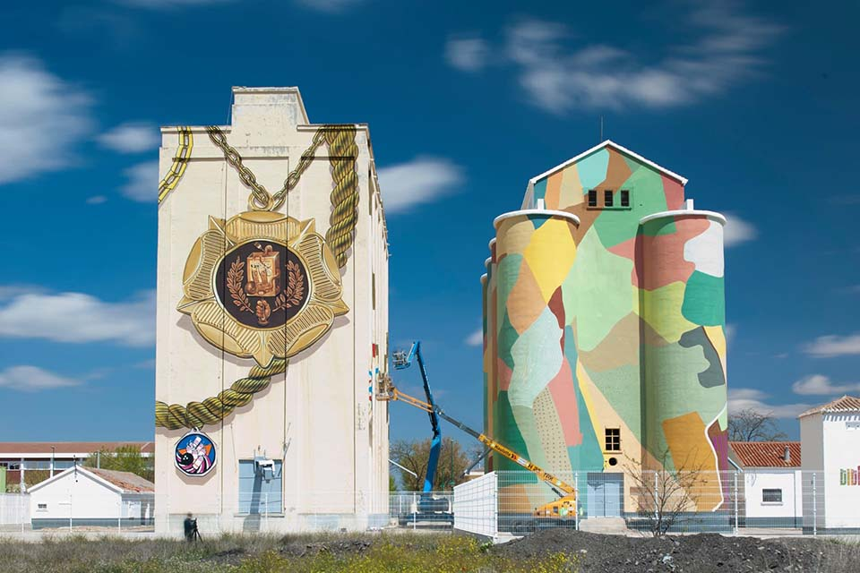 Two silos decorated by street art